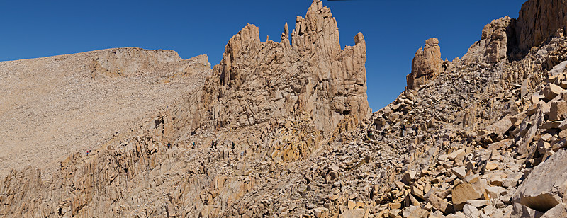 The summit of Mount Whitney can be recognized from the trail by the flat top with the stone building. The trail winds between towers and boulder fields for the last two miles along the ridge.