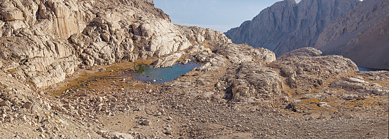 """This is Trail Camp viewed from the switchbacks. The lake is the last reliable water along the Mount Whitney Trail. (The higher springs and snow are seasonal.) In 2007, the dry preceding winter led to low stream flows, warmer than usual water temperature and greater than usual algae growth. By mid-September, flocks of ouzels and water pipets gathered to feed in the shallows on the population of invertebrates that fed on the algae.  <A HREF=""""http://dbdimages.smugmug.com/photos/200988501-O.jpg""""TARGET=""""blank"""">View Larger Image</A> (And use your browser's zoom if necessary.)"""