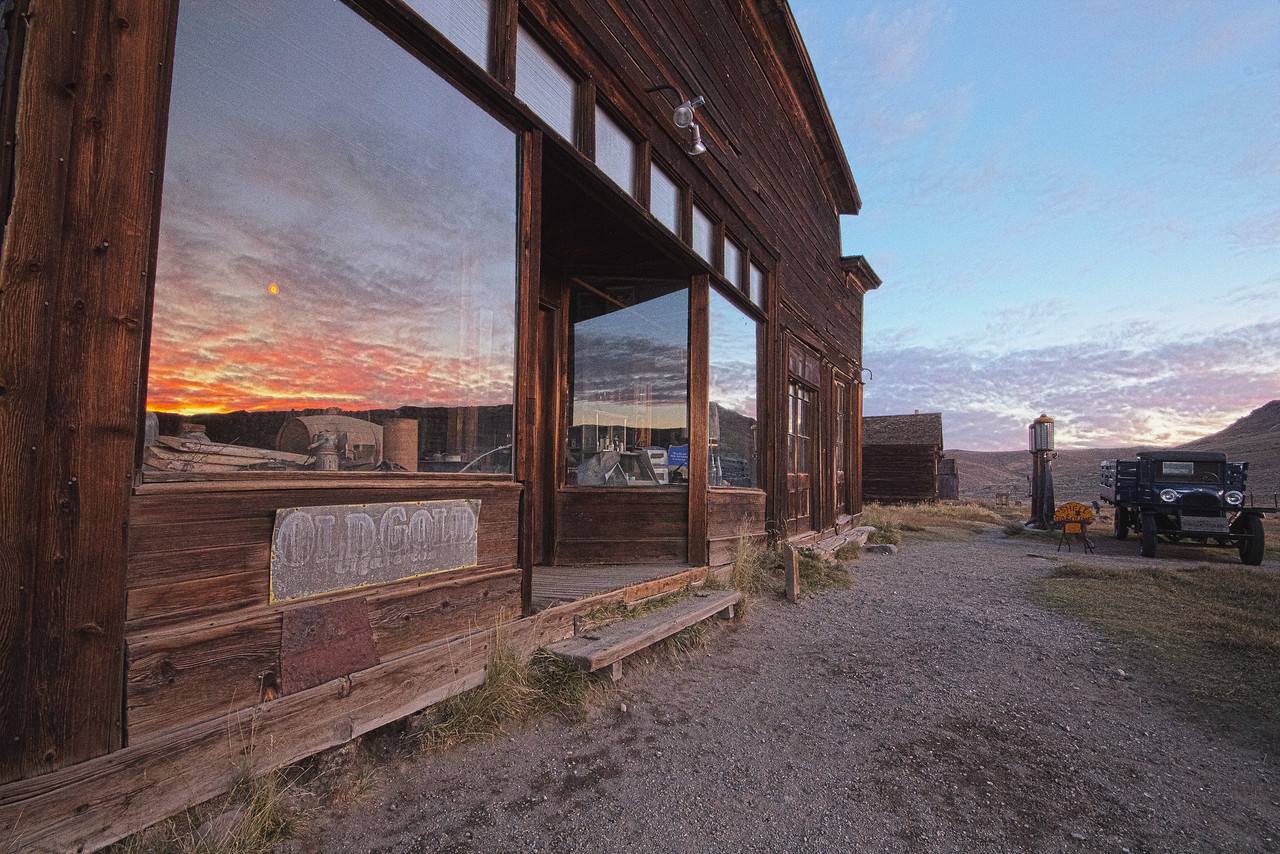 Sunrise reflection in Bodie store window.  The glowing bare light bulb inside is showing through the reflection
