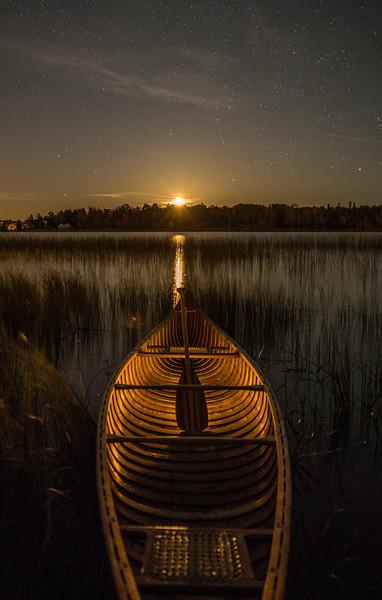 Yellow Moon Rising over Lit Canoe