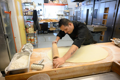 Jaime Ceballos, of Northside Bakery, rolls out dough and preps for cutting donuts in Avon on Tuesday.