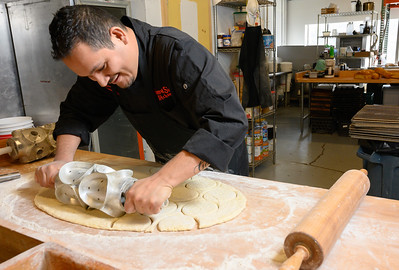 executive Pastry chef, Jaime Ceballos, rolls out dough for creme filled donuts at Northside's baking facility in Avon on tuesday.