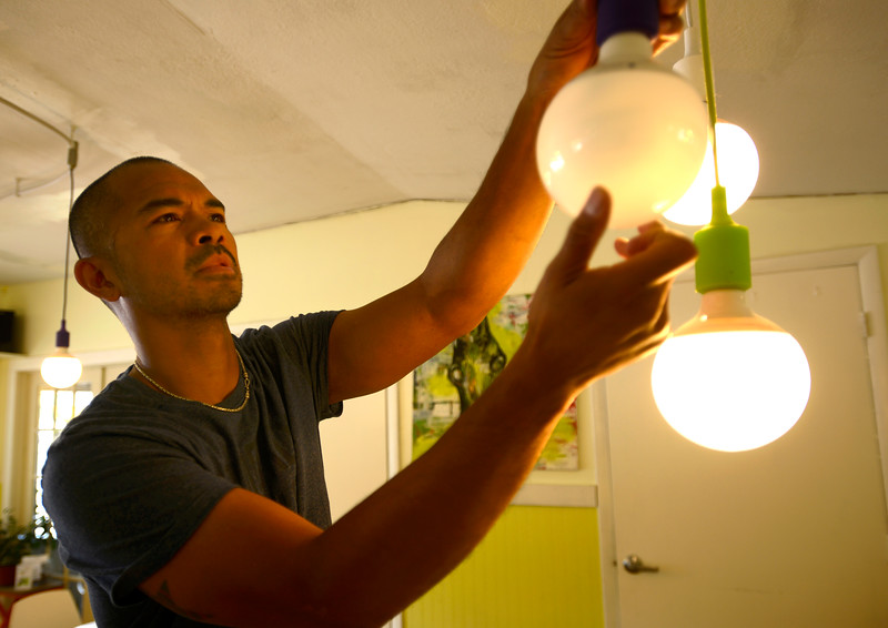 """Bobby Pangilinan, owner of Eats & Sweets replaces a lightbulb in his shop on Monday morning. To welcome the summer season, Eats & Sweets added a patio area and are adding locally sourced liquor to their menu offerings. For more photos go to  <a href=""""http://www.dailycamera.com"""">http://www.dailycamera.com</a><br /> <br /> Devi Chung For The Camera. June 13, 2016"""