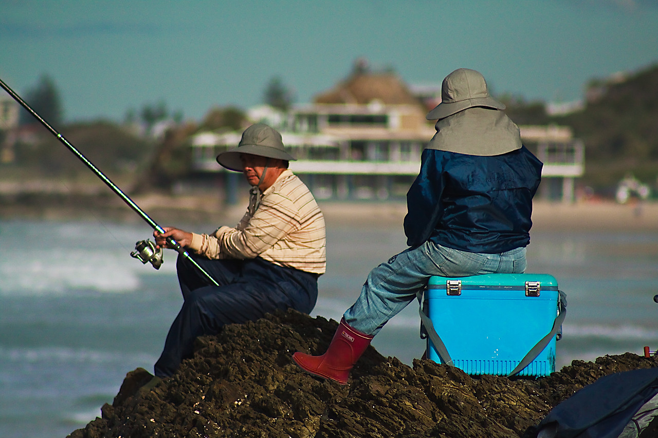 Two fishermen on the rocks at Currumbin beach, Australia
