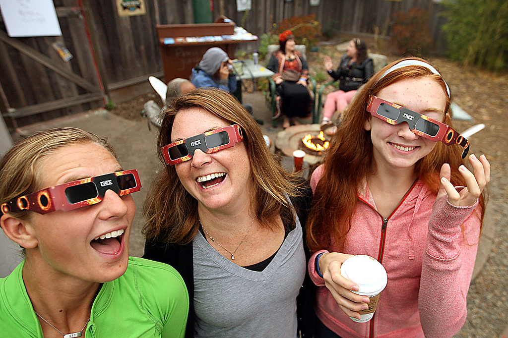 . Santa Cruz Mountains residents Kate Little, Rachel Powers and Lauren Powers make light of the disappointing fact they can\'t see through the fog at the summit to see the long-awaited eclipse.  (Dan  Coyro -- Santa Cruz Sentinel)