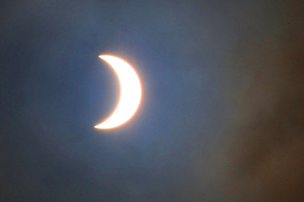 . The sun�s crescent shape shines through the clouds near the peak of Monday�s solar eclipse as seen from along Highway 17 near the Lexington Reservoir. (Shmuel Thaler � Santa Cruz Sentinel)