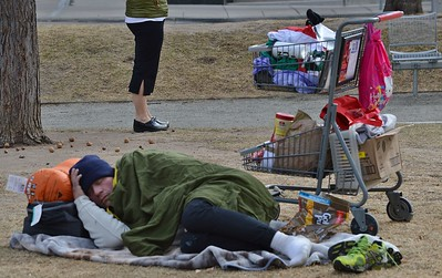 Homeless person with shopping cart full possessions, sleeping on the ground in downtown Denver park.