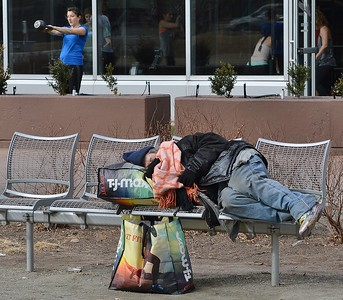 Homeless person sleeping on the ground in downtown Denver park as people in the background workout at a fitness center.