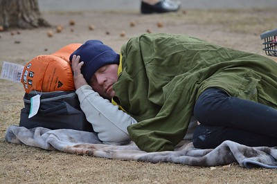 Homeless person sleeping on the ground in downtown Denver park.