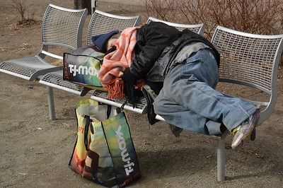 Homeless person sleeping on a bench in downtown Denver park.