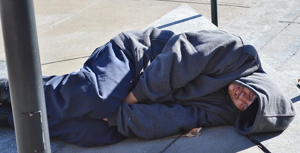 Homeless man sleeping on Denver street.