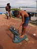 A boy weighs himself on a scale during the weekly riverside market in a small town in the Amazonian state of Para.(Australfoto/Douglas Engle)
