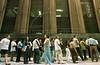 :Pedestrians walk past a line for job applicants in Sao Paulo. (Douglas Engle/Australfoto)