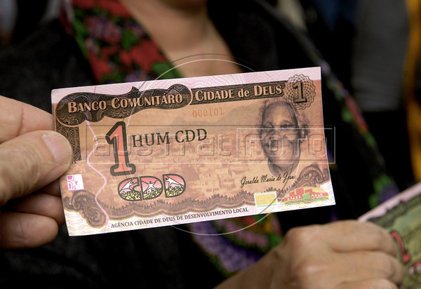 A functionary of Rio' district shows a bill, social currency Cidade de Deus, issued by the Community Bank of Cidade de Deus, Rio de Janeiro, Brazil, September 15, 2011.  The Brazilian favela City of God, received today the first branch of Community Bank, as a new experience to stimulate the activity economic in poor communities. (Austral Foto/Renzo Gostoli)