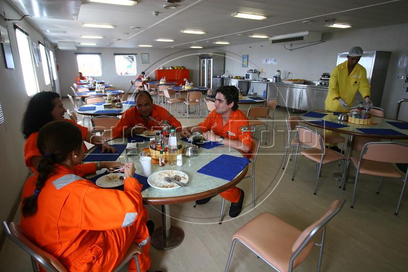 Petrobras employees eat in the cafeteria aboard the Petrobras P-43 Platform ship in the Campos Basin, of the Atlantic Ocean, off the coast of Rio de Janeiro, June 1, 2006.(Douglas Engle/Australfoto)