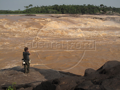 A photographer makes photos of the Teotonio rapids in the Madeira River near Porto Velho in Brazil's western Amazonian state of Rondonia. The rapids will disappear when the 7.7 billion dollar Santo Antonio dam goes into operation in 2011. Proponents say that Brazil needs more energy to grow and that the energy output per square kilometer of flooded area is one of the best ever. Detractors complain that fish stocks and indigenous populations will suffer.The dam will go online in December 2011 and make the Madeira River navegable for the first time - giving Bolivia access to the Atlantic ocean.  (Australfoto/Douglas Engle)