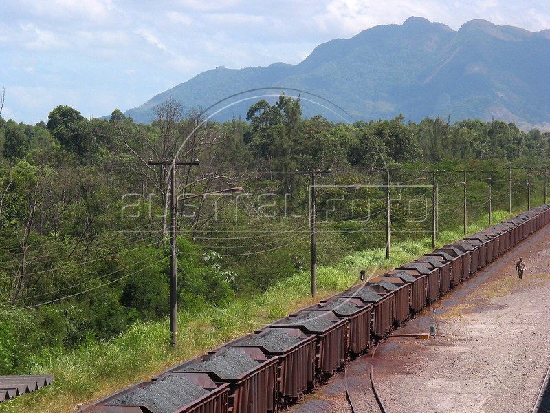 """A trainload of Iron Ore rolls into the Companhia Siderurgica de Tubar‹o (CST) in Serra, an industrial suburb of Vitoria in Brazil's coastal Espirito Santo state, Tuesday, March 11, 2003. The train brings in raw materials from neigboring Minas Gerais state and CST exports semi-finished steel (slabs) from a nearby port, earning a 20 percent share of the world market. The company, which began operations in 1983 and was privatized in 1992, also recently inaugurated a """"hot strip"""" mill as well for the domestic market. California Steel Industries is one of the partners along with Brazilian and Japanese investors. 49 percent of their slab exports go to North America while 23 percent go to Europe, 21 percent to Asia and seven percent to South America. With low production costs and huge reserves of iron ore, Brazil replaced Mexico as the number 2 US steel supplier in 2002, after Canada. (Australfoto/Douglas Engle)"""