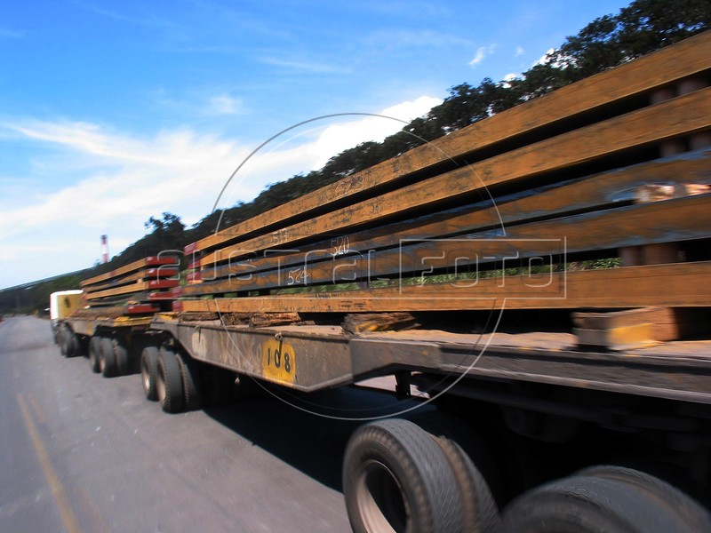 """A double-length truck carries semi-finished steel slabs to a nearby port at the Companhia Siderurgica de Tubar‹o (CST) in Serra, an industrial suburb of Vitoria in Brazil's Espirito Santo state, Tuesday, March 11, 2003. CST makes the semi-finished steel slabs for export and hold about 20 percent of the world market share. The company, which began operations in 1983 and was privatized in 1992, also recently inaugurated a """"hot strip"""" mill as well for the domestic market. California Steel Industries is one of the partners along with Brazilian and Japanese investors. 49 percent of their slab exports go to North America while 23 percent go to Europe, 21 percent to Asia and seven percent to South America. With low production costs and huge reserves of iron ore, Brazil replaced Mexico as the number 2 US steel supplier in 2002, after Canada. (Australfoto/Douglas Engle)"""
