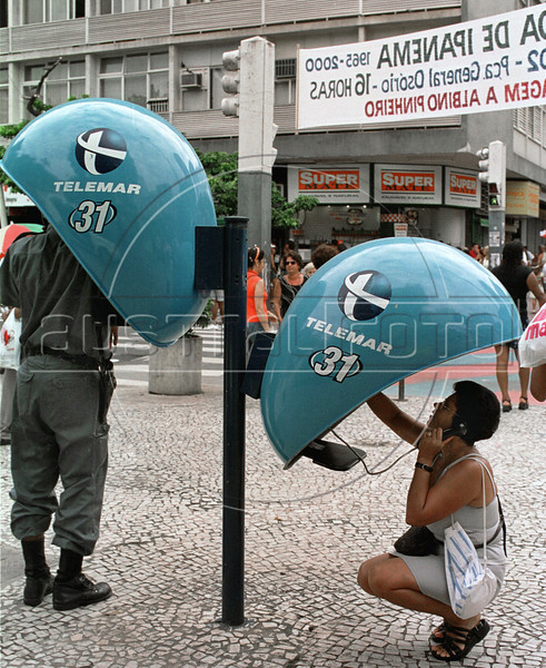 A policeman, left, and a woman speak on public phones in Ipanema, Rio de Janeiro, Brazil, Mars 1, 2000. (Austral Foto/Renzo Gostoli)