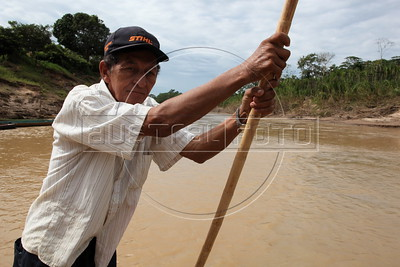 A man navegates the Acre River, which separates Peru from Brazil near where the Transoceanic Highway passes. Financed in part by Brazil, and built by a consortium which includes Brazilian construction company Oderbrecht, the US$1.3 billion highway will link Peru's Pacific ports, and thus China, with the regional powerhouse of Brazil, poised to become the 5th largest economy in the world. (Australfoto/Douglas Engle)