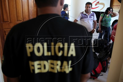A Brazilian federal Police office waits to check buss passengers arriving into Brazil from Peru on the Transoceanic Highway in Brazil's Amazonian state of Acre, which borders Peru. Financed in part by Brazil, and built by a consortium which includes Brazilian construction company Oderbrecht, the US$1.3 billion highway will link Peru's Pacific ports, and thus China, with the regional powerhouse of Brazil, poised to become the 5th largest economy in the world. (Australfoto/Douglas Engle)