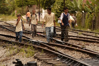 "Boys walk on the tracks of the Trem Metropolitano de Maceio (Maceio Metropolitan Train), in Maceio, Alagoas state, Brazil. Originally founded in 1884 as the ""Alagoas Railway"" by an Englishman, The 32 km line is now operated by the Companhia Brasileria de Trens Urbanos (CBTU) and runs from Macei— to the town of Loureno de Albuquerque. Eight trains make the 1 hour trip, each direction, daily. The trip currently costs 50 Brazilian cents (about 25 US cents) and is a lifeline for residents of the simple bedroom communities along it. It also make for a good tourism alternative in the region, since the line passes by some of the lagoons which give the state its name. The CBTU operated all urban trains in Brazil until several were sold off or given operating concessions in the 1990s.(Australfoto/Douglas Engle)"