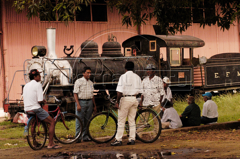 Men stand near a Baldwin locomotive of the historic, and largely abandoned, Madeira-Mamore Railroad in Porto Velho, in Brazil's Amazonian state of Rondonia, Oct. 25, 2004. About Six thousand workers died building the railroad between 1871 and 1912. Built during the rubber boom to bypass a series of rapids on the Mamore river, it gave nearby Bolivia an outlet to the Atlantic Ocean through the naviagle river system below the rapids.  It opened about the same time that the rubber boom went bust and It was kept active until 1931, when it was taken over by the Brazilian government. In 1972 it shut down permanently, except for weekend tourist trips. In 2000 a mudslide washed out part of the remaining line and it has not operated since.(Australfoto/Douglas Engle)
