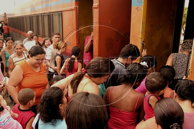 "Passengers rush to board the Trem Metropolitano de Maceio (Maceio Metropolitan Train), in Maceio, Alagoas state, Brazil. Originally founded in 1884 as the ""Alagoas Railway"" by an Englishman, The 32 km line is now operated by the Companhia Brasileria de Trens Urbanos (CBTU) and runs from Macei— to the town of Loureno de Albuquerque. Eight trains make the 1 hour trip, each direction, daily. The trip currently costs 50 Brazilian cents (about 25 US cents) and is a lifeline for residents of the simple bedroom communities along it. It also make for a good tourism alternative in the region, since the line passes by some of the lagoons which give the state its name. The CBTU operated all urban trains in Brazil until several were sold off or given operating concessions in the 1990s.(Australfoto/Douglas Engle)"