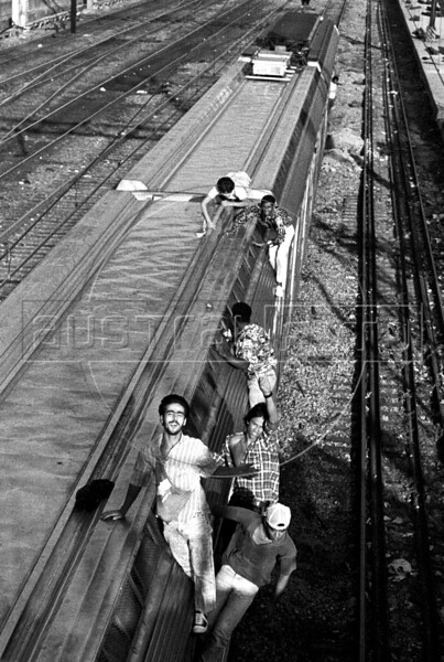 """Illegal train passengers """"surf"""" on one of the government-owned metropolitan commuter trains in Rio de Janeiro in this 1988 photograph. Hundreds of people used to take the train without paying before the trains were privatized, in what was considered part sport, and part dare and part commute. The Supervia company took control of Rio commuter railways in 1998, implementing modernization measures, such as the banning of train surfing, line and station improvements and new rail cars. (Austral Foto/Renzo Gostoli)"""