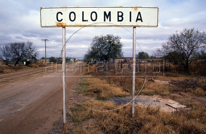 A sign welcomes travelers to Colombia, Nuevo Leon state, Mexico, across the border from Laredo, Texas, USA. The town, planned to compete with other border crossings, represents the limited border (9 miles) that the Mexican state of Nuevo Leon shares with the state of Texas, particularly with Webb County and the City of Laredo. Future plans for the town include a new international railroad bridge, a new toll-free road connecting Colombia to the existing roads linking Monterrey and the port of Laredo, and a new cargo airport.<br /> (Australfoto/Douglas Engle)