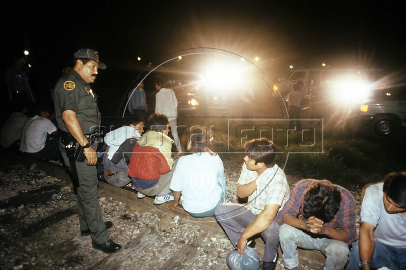 A US Border Patrol agent standa guard over detained Mexicans near Laredo, Texas.(Australfoto/Douglas Engle)