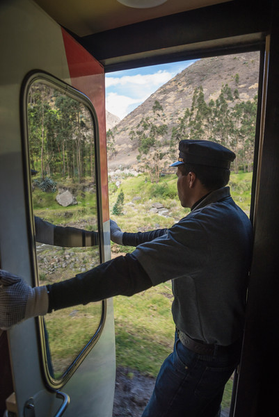 Conductor stands in open doorway of Nariz del Diablo train, Alausi, Ecuador