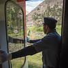 Conductor stands in open doorway of Nariz del Diablo train, Alausi, Ecuador