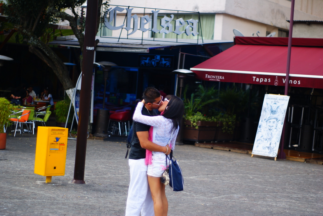 A couple passionately kisses in the middle of a square - Quito, Ecuador.  Snogging and the embrace of two lovers in Quito, Ecuador.