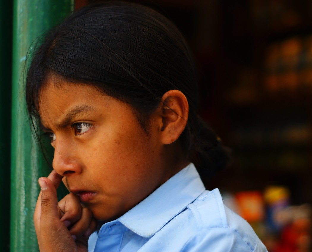 A cute Ecuadorian girl picking her nose - Quito, Ecuador.  This is a travel photo from Quito, Ecuador.