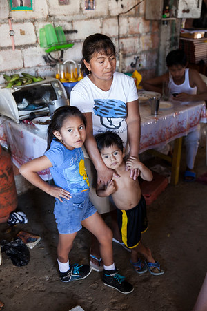 A mother and her three children in the family's kitchen.  The young girl has a deformity with her right foot which has been operated on by a international NGO.  Her father explained to me that NGO's have helped his family more than his own country government.