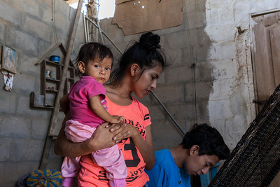 A young mother  speaks with a health census volunteer.  Her young child is 14 months old but weighs less than 15 pounds due to a intestinal infection.