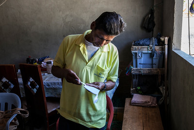 A man in Anconcito uses daylight from the window to read instructions from the clinic physician.