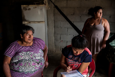 A young girl sits in the family kitchen completing a health census form as her mother and sister gaze out the window.