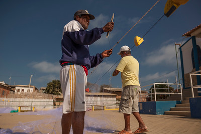 Fisherman repair their nets in preparation of a night of fishing off the coast of Southern Ecuador.