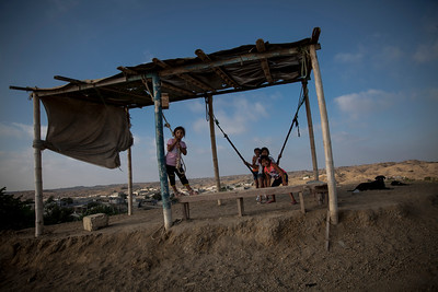 Children play on a hilltop structure overlooking the town of Anconcito.
