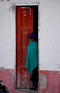 Old lady looking out of the front door, Ecuador.