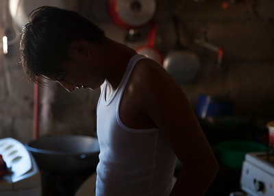 A young man stands in his kitchen in Anconcito, Ecuador.