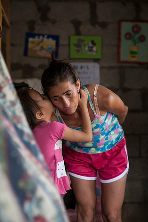 A young girl whispers a secret to her mother.