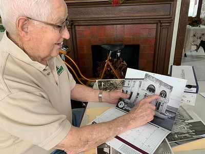 Ed Powell in 2019 uses MFB's Centennial-year calendar to point to the location of his first Michigan Elevator Exchange office, on the second floor or Michigan Farm Bureau's first home office, at 221 N. Cedar Street in Lansing.