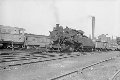 2018.15.N68F.4950--ed wilkommen 6x9 neg--CMStP&P--steam locomotive 0-6-0 I5a 1520 in yard FM demonstrator diesel in background--Milwaukee WI--1948 0700