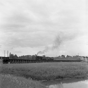 2018.15.N65B.8255--ed wilkommen 120 neg--CStPM&O--steam locomotive 0-8-0 on long wooden trestle with one freight car train action--Superior WI--c1955. This train is coming up from Omaha's Itasca Merchandise Dock and heading back to Itasca yard. The long curving trestle goes over Bluff Creek and U.S. Highway 2/53. The overpass in the distance is the NP Ashland line. Camera is pointed north-northwest. Ed Wilkommen was standing on the newly relocated U.S. Highway 2/53 alignment. The Omaha had a huge grain elevator, warehouses, and other terminal facilities on this dock.