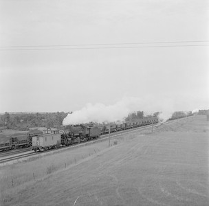 2018.15.N76.6088A--ed wilkommen 120 neg--DM&IR--steam locomotive 2-8-2 helper with caboose in yard scene--location unknown--no date