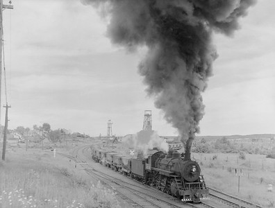 2018.15.N76.7907--ed wilkommen 3X4 neg--DM&IR--steam locomotive 2-8-0 K 1218 with string of ore empties in yard action--Ely MN--1960 0700