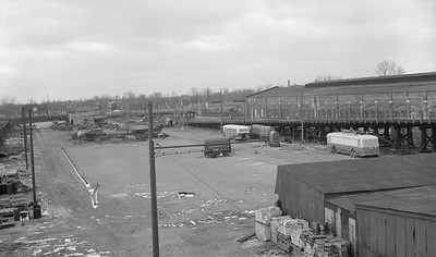 2018.15.N99E.8004--ed wilkommen 116 neg--CTA--Hamlin Yard shops view--Chicago IL--1960s. Used at this time by work trains for track material. Track at left foreground crossing Lake Street at grade to access West Shops where special track work was/is constructed. Rail connection to this yard has since been removed. Now used for storage.